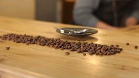 Κινηματογράφηση σε πρώτο πλάνο των φασολιών καφέ σε έναν ξύλινο πίνακα σε μια καφετερία απόθεμα βίντεο