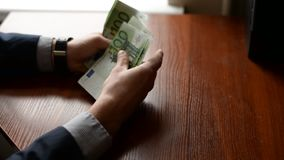 Κινηματογράφηση σε πρώτο πλάνο των χεριών ενός επιχειρηματία που μετρούν εκατό ευρο- λογαριασμούς σε έναν πίνακα απόθεμα βίντεο