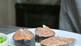 Κινηματογράφηση σε πρώτο πλάνο των χεριών ενός κοριτσιού μαγείρων που προετοιμάζει το φρέσκο πότισμα πεστροφών σολομών ψαριών με  απόθεμα βίντεο