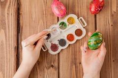 Κινηματογράφηση σε πρώτο πλάνο των χεριών της γυναίκας που χρωματίζουν ένα αυγό Πάσχας στο ξύλινο υπόβαθρο απεικόνιση αποθεμάτων
