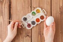Κινηματογράφηση σε πρώτο πλάνο των χεριών της γυναίκας που χρωματίζουν ένα αυγό Πάσχας στο ξύλινο υπόβαθρο διανυσματική απεικόνιση