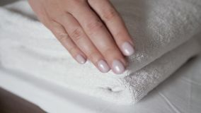 Κινηματογράφηση σε πρώτο πλάνο των χεριών που βάζουν το σωρό των φρέσκων άσπρων πετσετών λουτρών στο σεντόνι Μακροεντολή δωματίου απόθεμα βίντεο