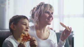 Κινηματογράφηση σε πρώτο πλάνο mom με το γιο που τρώει την πίτσα και που προσέχει τη TV απόθεμα βίντεο