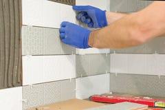 Κινηματογράφηση σε πρώτο πλάνο tiler του χεριού που βάζει το κεραμικό κεραμίδι στον τοίχο στην κουζίνα, ανακαίνιση, επισκευή, κατ στοκ εικόνες