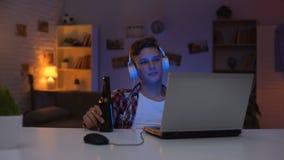 Κινηματογράφος προσοχής αγοριών εφήβων στο lap-top, μπύρα κατανάλωσης, τρώγοντας τα πρόχειρα φαγητά, που σπαταλούν το χρόνο φιλμ μικρού μήκους