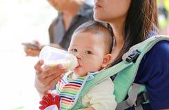 Κινηματογραφήσεων σε πρώτο πλάνο ασιατικό αγοράκι νηπίων μητέρων φέρνοντας και κράτημα του μπουκαλιού γάλακτος του παιδιού της στοκ φωτογραφίες
