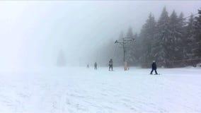 Κινούμενος ανελκυστήρας ρυμούλκησης σχοινιών με τους σκιέρ στη σκοτεινή χιονώδη ομιχλώδη ημέρα στα βουνά Δημοκρατία της Τσεχίας,  απόθεμα βίντεο