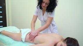 Κλίση επάνω της νέας γυναίκας που παίρνει το επαγγελματικό αντι μασάζ cellulite στην πλάτη φιλμ μικρού μήκους