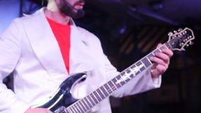 Κλείστε αυξημένος ενός κιθαρίστα παίζει την κιθάρα στο στάδιο φιλμ μικρού μήκους