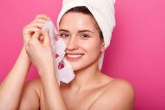 Κλείστε αυξημένος της ελκυστικής χαμογελώντας γυναίκας αφαιρεί τη μάσκα εγγράφου από το πρόσωπο, που ικανοποιεί με την επίδρασή τ στοκ φωτογραφίες με δικαίωμα ελεύθερης χρήσης