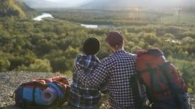 Κλείστε αυξημένος της όμορφης συνεδρίασης ζευγών στο έδαφος στο βουνό φιλμ μικρού μήκους
