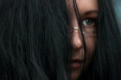 Κλείστε αυξημένος του θηλυκού προσώπου που καλύπτεται με τη μαύρη τρίχα στοκ φωτογραφία