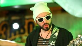 Κλείστε αυξημένος του κιθαρίστα στα γυαλιά ηλίου που τραγουδούν και που παίζουν απόθεμα βίντεο