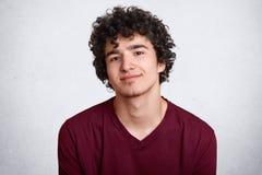 Κλείστε αυξημένος του σγουρού μαλλιαρού ευρωπαϊκού εφήβου με λίγη γενειάδα, φορά το καφέ πουκάμισο Νεολαίες που χαμογελούν τις αρ στοκ εικόνα