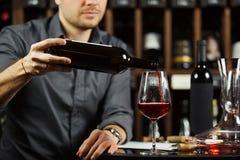 Κλείστε αυξημένος του πιό sommelier χύνοντας κόκκινου κρασιού από το μπουκάλι στο γυαλί στοκ φωτογραφίες
