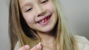 Κλείστε - επάνω ενός χαριτωμένου χαμογελώντας κοριτσιού, ένα παιδί που παρουσιάζει σχισμένο κυνόδοντα γάλακτος στο χέρι της και μ απόθεμα βίντεο