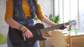 Κλείστε επάνω νέο rocker γυναικών παίζοντας την ηλεκτρική κιθάρα στο σύγχρονο διαμέρισμα απόθεμα βίντεο