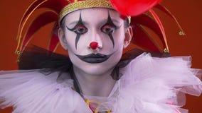 Κλείστε επάνω σοβαρός θηλυκός jester με το makeup και ένα καπέλο ενώ ένα μπαλόνι πετά κοντά στο πρόσωπό της απόθεμα βίντεο