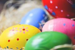 Κλείστε επάνω τα ζωηρόχρωμα αυγά Πάσχας στη φωλιά καλαθιών στοκ εικόνες