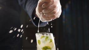 Κλείστε επάνω τον αρχιμάγειρα χεριών που συμπιέζει τον ασβέστη επάνω στο φρέσκο κοκτέιλ mojito σε σε αργή κίνηση χυμός που στάζει απόθεμα βίντεο