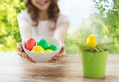 Κλείστε επάνω του κοριτσιού με το κύπελλο των χρωματισμένων αυγών Πάσχας στοκ εικόνες