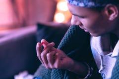 Κλείστε επάνω του νεαρού άνδρα που καλύπτεται με ένα κάλυμμα που εξετάζει το κόκκινο χάπι, το οποίο πρόκειται να πιει στοκ εικόνες με δικαίωμα ελεύθερης χρήσης