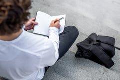 Κλείστε επάνω του σπουδαστή στα βήματα του σύγχρονου κειμένου οικοδόμησης και γραψίματος στο σημειωματάριο στοκ φωτογραφίες