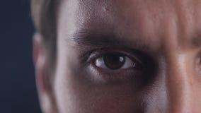 Κλείστε επάνω το καφετί μάτι του νέου καυκάσιου ατόμου που ανοίγει το μάτι του και που εξετάζει το φακό καμερών στο μαύρο misty υ φιλμ μικρού μήκους