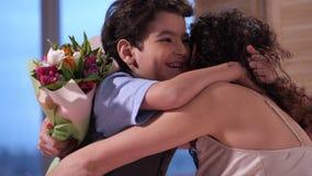 Κλείστε επάνω το λατρευτό γιο που παρουσιάζει τα λουλούδια στο mom φιλμ μικρού μήκους