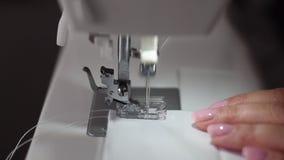 Κλείστε επάνω το μήκος σε πόδηα μιας γυναίκας που ράβει ένα άσπρο ύφασμα βαμβακιού με μια ράβοντας μηχανή - σε αργή κίνηση φιλμ μικρού μήκους