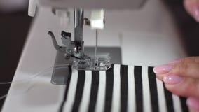 Κλείστε επάνω το μήκος σε πόδηα μιας νέας γυναίκας που ράβει ένα άσπρος-μαύρο ύφασμα βαμβακιού λωρίδων με μια σύγχρονη ράβοντας μ απόθεμα βίντεο