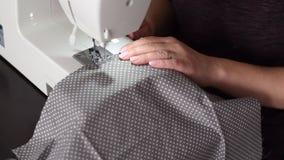 Κλείστε επάνω το μήκος σε πόδηα μιας νέας γυναίκας που ράβει ένα γκρίζο άσπρο ύφασμα βαμβακιού σημείων με μια ράβοντας μηχανή - β φιλμ μικρού μήκους