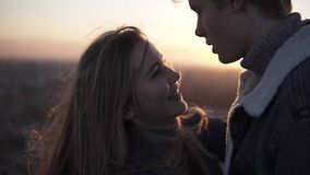 Κλείστε επάνω το μήκος σε πόδηα του ρομαντικού νέου ζεύγους που στέκεται πρόσωπο με πρόσωπο αναδρομικά φωτισμένου από τον ήλιο με φιλμ μικρού μήκους