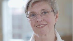 Κλείστε επάνω το πορτρέτο της ανώτερης γυναίκας με τα γυαλιά που φαίνεται κεκλεισμένων των θυρών με το ευχάριστο χαμόγελο στο εσω απόθεμα βίντεο