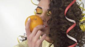 Κλείστε επάνω το πορτρέτο του νέου εύθυμου χαμογελώντας κοριτσιού με φωτεινό αποτελεί κρατά και παίζει με το πορτοκάλι και μετά α φιλμ μικρού μήκους