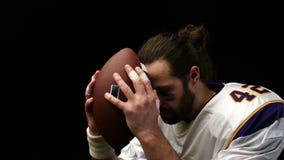 Κλείστε επάνω το πορτρέτο του φορέα αμερικανικού ποδοσφαίρου με τη σφαίρα απόθεμα βίντεο
