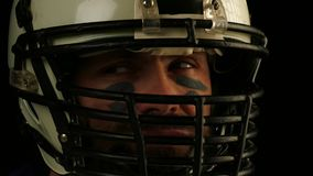 Κλείστε επάνω το πορτρέτο του φορέα αμερικανικού ποδοσφαίρου στο κράνος φιλμ μικρού μήκους