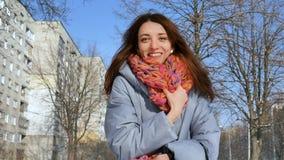 Κλείστε επάνω το πορτρέτο του χαμογελώντας ενήλικου κοριτσιού στο μπλε παλτό και του ζωηρόχρωμου πλεκτού μαντίλι κατά τη διάρκεια απόθεμα βίντεο