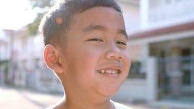 Κλείστε επάνω το πρόσωπο της εύθυμης ασιατικής συγκίνησης ευτυχίας παιδιών που στέκεται υπαίθριας απόθεμα βίντεο