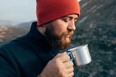 Κλείστε επάνω υπαίθρια το πορτρέτο του νεαρού άνδρα που πίνει το καυτό ποτό στα βουνά, χαλαρώνοντας μετά από την οδοιπορία στοκ φωτογραφία