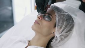 Κλείστε το cosmetologist αποτελεί το λέιζερ την αγγειακή αφαίρεση στο πρόσωπο της γυναίκας με τον ειδικό εξοπλισμό φιλμ μικρού μήκους