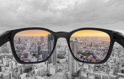 Κοίταγμα μέσω των γυαλιών στην άποψη πόλεων στο ηλιοβασίλεμα Γυαλιά αχρωματοψίας, έξυπνη τεχνολογία γυαλιών στοκ εικόνα με δικαίωμα ελεύθερης χρήσης