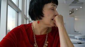 Κομψή ηλικίας γυναίκα, καυκάσιο έθνος, τρυπημένη αναμονή τα διαταγμένα τρόφιμα απόθεμα βίντεο