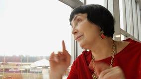Κομψή ηλικίας γυναίκα, καυκάσιο έθνος, που κοιτάζει στο παράθυρο απόθεμα βίντεο
