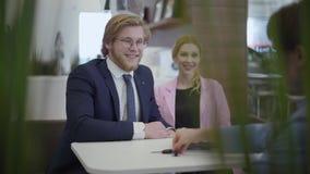 Κομψοί άνδρας και γυναίκα στα επίσημα κοστούμια που κάθονται στον πίνακα που αγοράζει το νέο αυτοκίνητο στη σύγχρονη έκθεση αυτοκ απόθεμα βίντεο