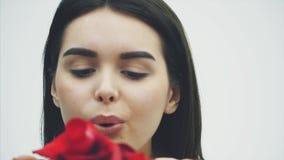 Κομψότητα και τρυφερότητα Η όμορφη νέα γυναίκα τρίχας brunette φυσά τα πέταλα της γης Εξετάζοντας τη κάμερα, ενώ απόθεμα βίντεο