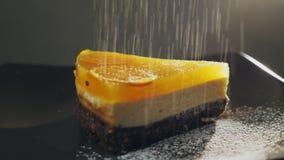 Κονιοποιημένες πτώσεις ζάχαρης πάνω από ένα κέικ και ένα πιάτο σε σε αργή κίνηση απόθεμα βίντεο