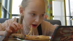 Κορίτσι εφήβων πορτρέτου που τρώει την τυροειδή πίτσα με το σαλάμι στα ιταλικά καφές γρήγορου φαγητού απόθεμα βίντεο