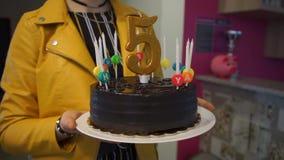 Κορίτσι σε ένα κίτρινο σακάκι που κρατά ένα κέικ σοκολάτας απόθεμα βίντεο