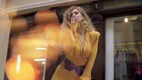 Κορίτσι σε ένα κίτρινο φόρεμα και κόκκινη τοποθέτηση παλτών για τη κάμερα στη μετάβαση φιλμ μικρού μήκους